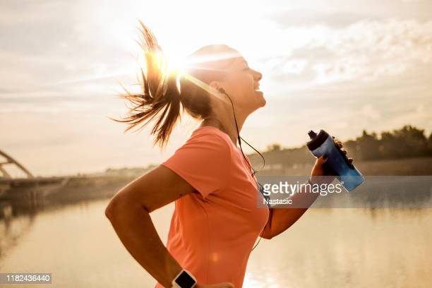 young woman running against morning sun - jogging stock pictures, royalty-free photos & images