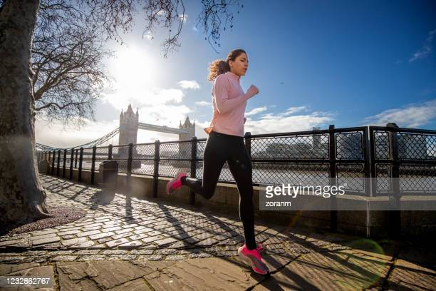 young woman running alone by the river thames - improvement stock pictures, royalty-free photos & images