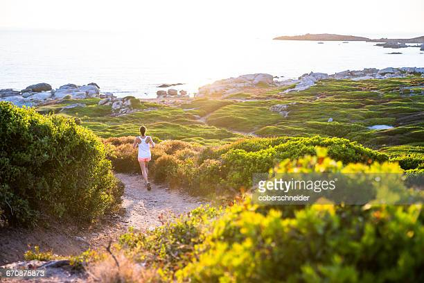 Young Woman running along a trail, Corsica, France