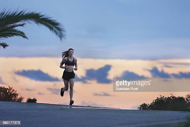 Young woman running along coastline at sunset