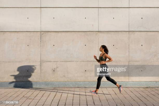 young woman running along concrete wall in the city - laufwettbewerb der frauen stock-fotos und bilder