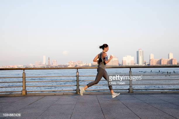 young woman running along hudson river - track event stock pictures, royalty-free photos & images