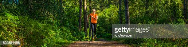 Young woman running along picturesque forest trail through ferns panorama