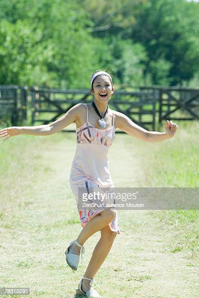 Young woman running along rural path, smiling at camera