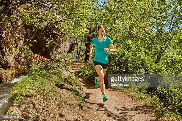 Young woman running along rural pathway, Meran, South Tyrol, Italy