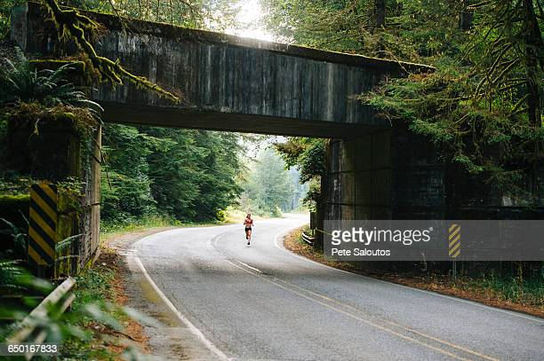 Young woman running along rural road