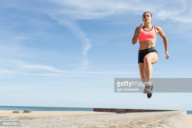 young woman running along sea wall, mid air - sprinting stock photos and pictures