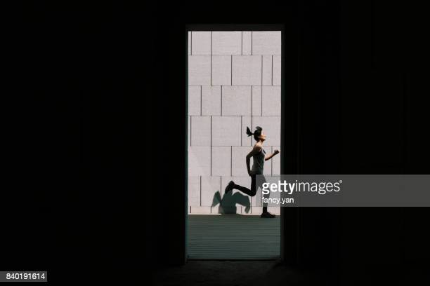 young woman running along the wall - center athlete stock pictures, royalty-free photos & images