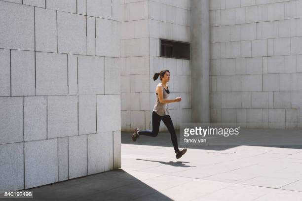 young woman running along the wall