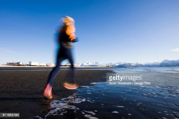 a young woman running along the waters edge - home run ストックフォトと画像