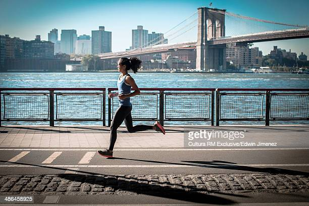 Young woman running along waterfront, New York, USA