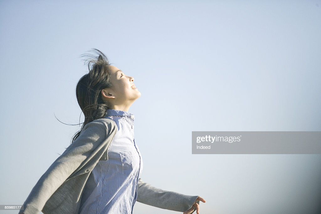 Young woman running and looking at sky, side view : Stock Photo