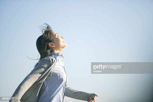 Young woman running and looking at sky, side view