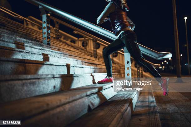 young woman running at night in a urban city area - gray shoe stock pictures, royalty-free photos & images