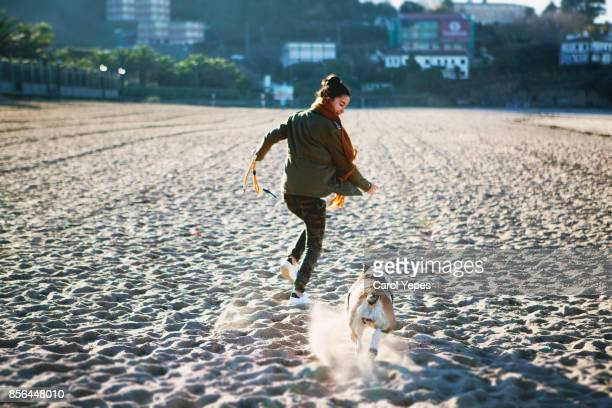 young woman running at the beach with her dog