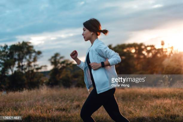 young woman running at the park at sunset - one woman only stock pictures, royalty-free photos & images
