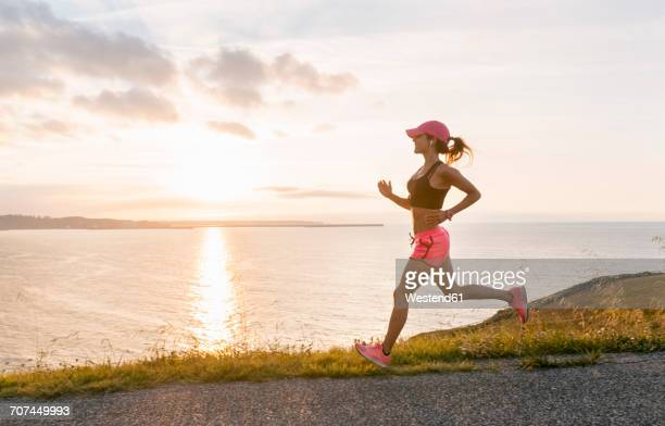 young woman running at the sea - forward atlet bildbanksfoton och bilder