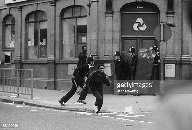 A young woman running away as policemen take cover in the doorway of a National Westminster Bank during the Brixton Riot of 11th April 1981