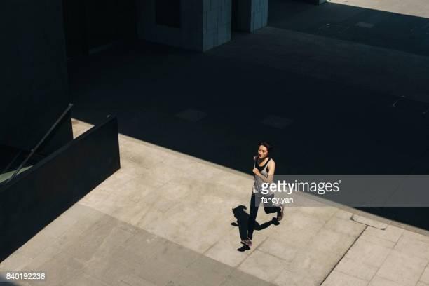 young woman running below building