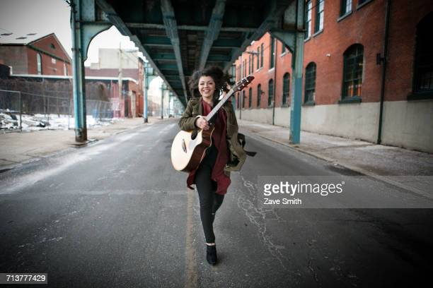 Young woman running below elevated road with acoustic guitar