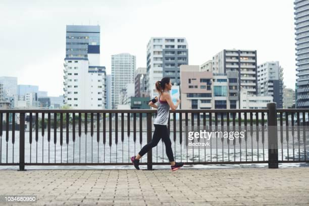 夕暮れ時に川で走っている若い女性 - 川岸 ストックフォトと画像