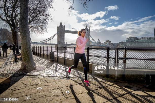 young woman running down the pier by the river thames - water's edge stock pictures, royalty-free photos & images
