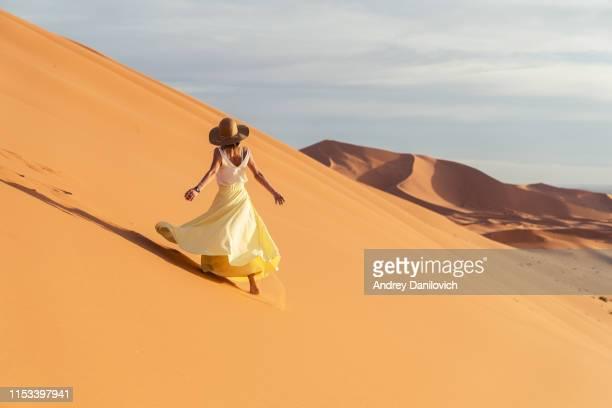 een jonge vrouw die loopt van de top van een zandduin. zonsopgang in de merzouga (sahara) woestijn. - wit hemd stockfoto's en -beelden