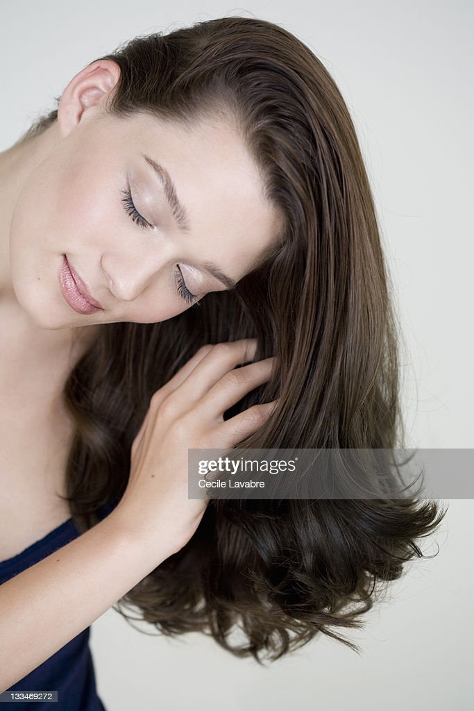 Young woman running hand through her long hair : Stock Photo