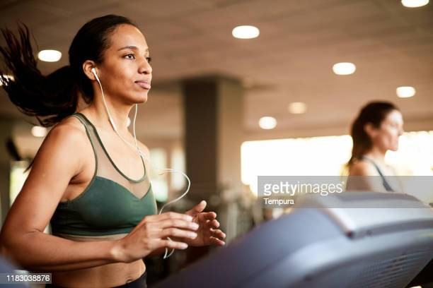 young woman running in a treadmill and listening to music. - cardiovascular exercise stock pictures, royalty-free photos & images