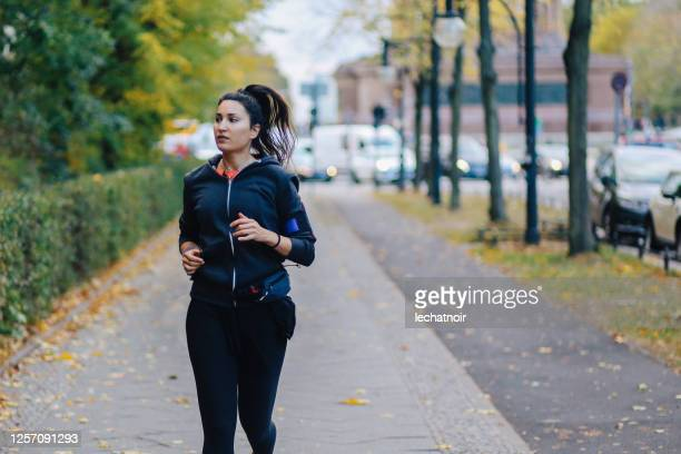 young woman running in berlin - one young woman only stock pictures, royalty-free photos & images