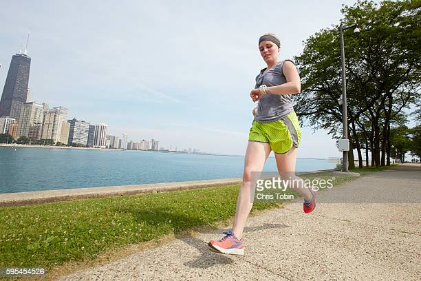 Young woman running in city park along lake