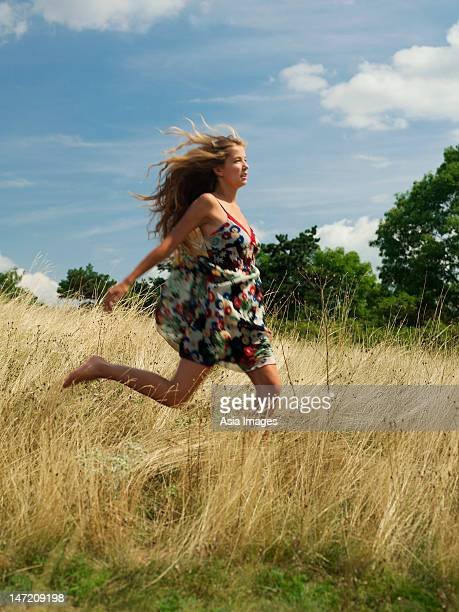 Young woman running in grassy field