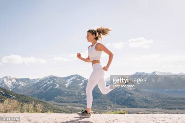young woman running in mountain setting - correr fotografías e imágenes de stock