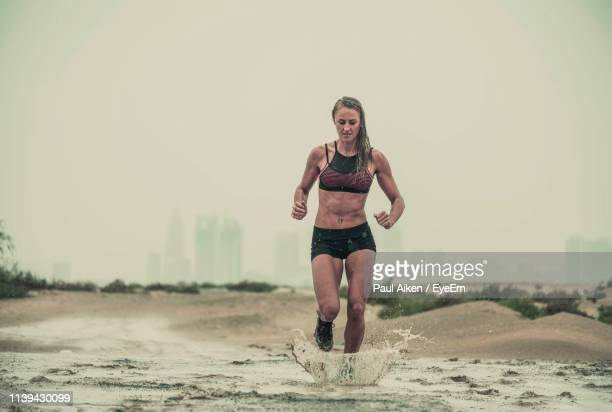 young woman running in mud against sky - aikāne stock pictures, royalty-free photos & images