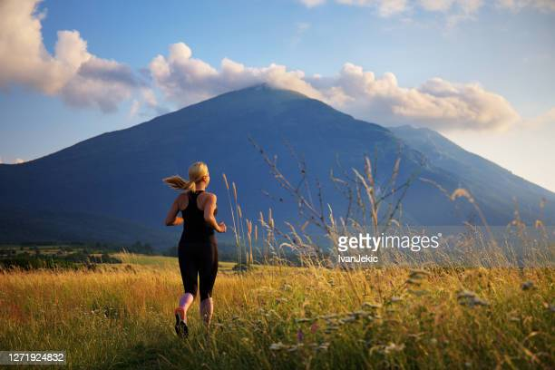 young woman running in nature by the mountain - ivanjekic stock pictures, royalty-free photos & images