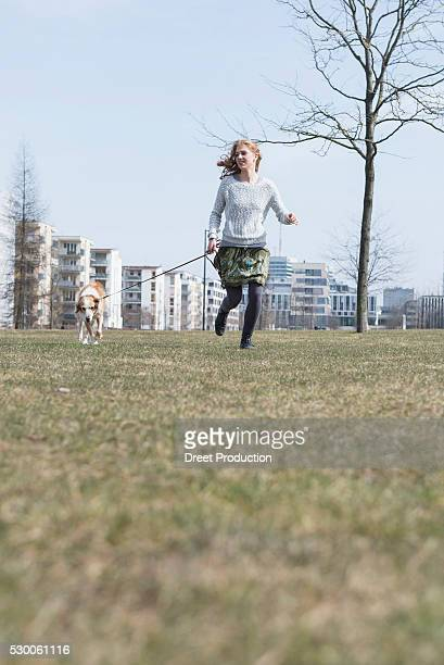 Young woman running in park with dog, Munich, Bavaria, Germany