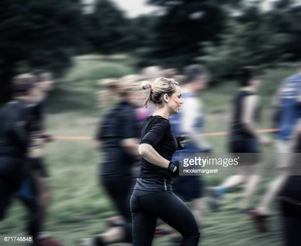 young woman running in race - obstacle course stock pictures, royalty-free photos & images