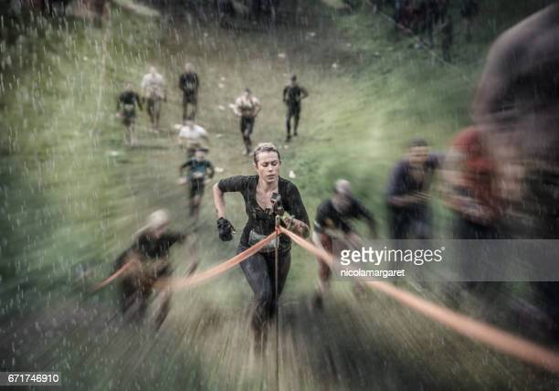 young woman running in race - obstacle course stock photos and pictures