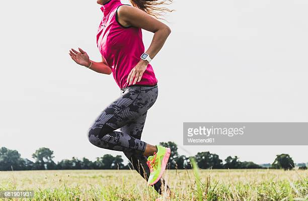 Young woman running in rural landscape