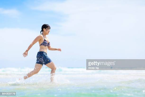 Young Woman Running In Sea Happily