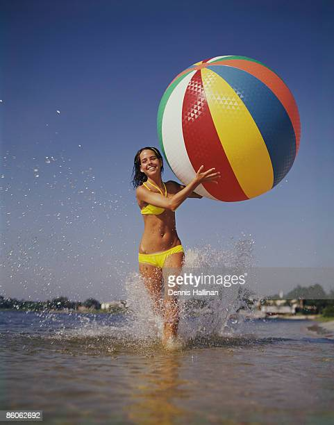 Young Woman Running in Surf with Beach Ball