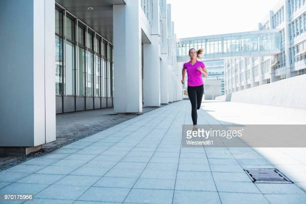 young woman running in the city - approaching stock pictures, royalty-free photos & images