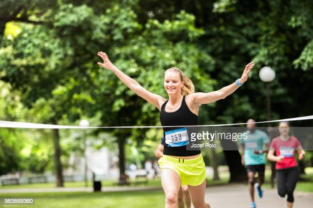 young woman running in the crowd crossing the finish line. - women's field event stock pictures, royalty-free photos & images