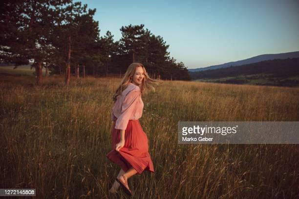 young woman running in the field - natürliche schönheit personen stock-fotos und bilder