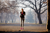 young woman running park shallow dof