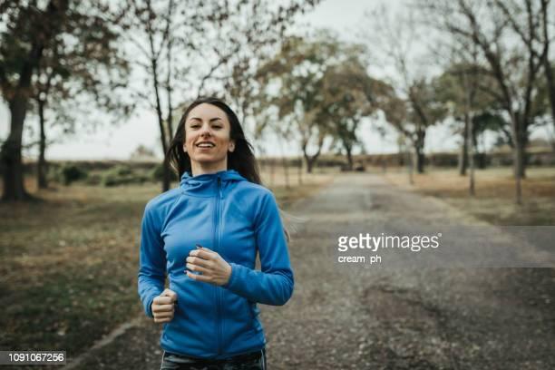 young woman running in the public park - questão da mulher imagens e fotografias de stock