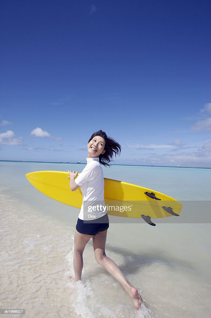 Young Woman Running in the Sea and Carrying a Surfboard : Stock Photo