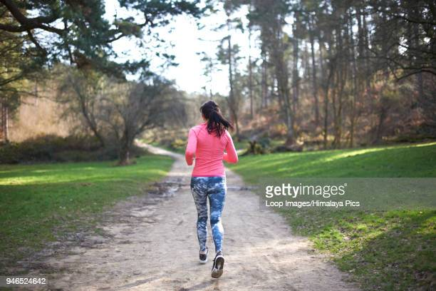 A young woman running in the woods