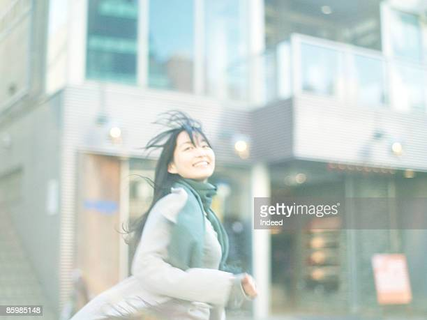Young woman running in town, smiling, portrait