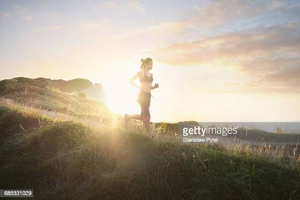 young woman running near ocean - ochtend stockfoto's en -beelden